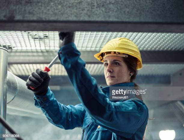 craftswoman wearing hard hat at work - gleichheit stock-fotos und bilder