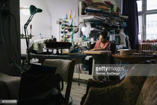Craftswoman Working On Sewing Machine In Workshop