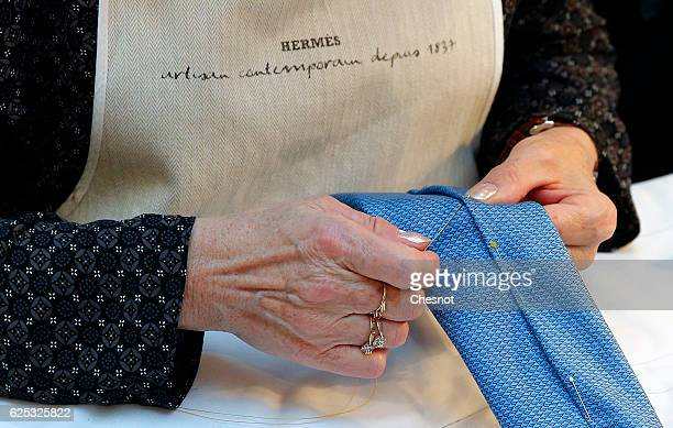 A craftswoman works on a tie of the luxury brand Hermes displayed during the 'Hermes hors les murs' event on November 23 2016 in Paris France The...