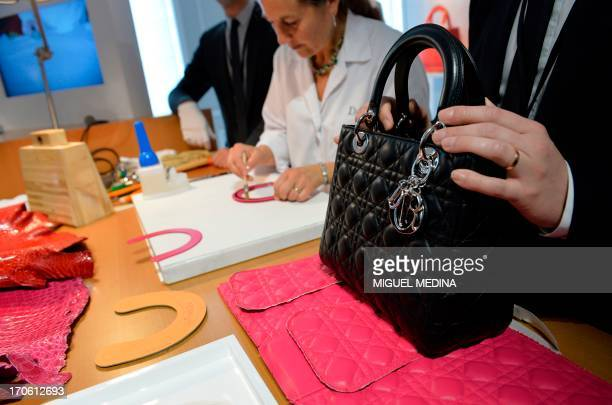 A craftswoman works on the handle of a bag at the accessories workshop of French luxury brand Dior in Paris on June 15 2013 AFP PHOTO / MIGUEL MEDINA