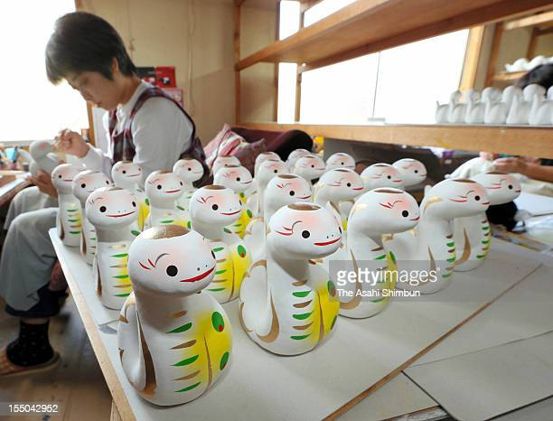 A craftwoman produces papiermache statue featuring snake the oriental zodiac sign for the coming year 2013 on october 30 2012 in Nishiaizu Fukushima...