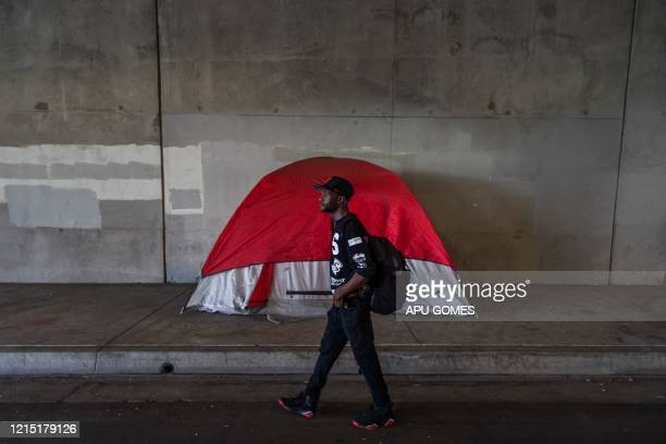 Crag 28 yearsold walks to get his phone back after recharging it in a spot next to his tent under the bridge of the 110 Freeway at 37th Street during...