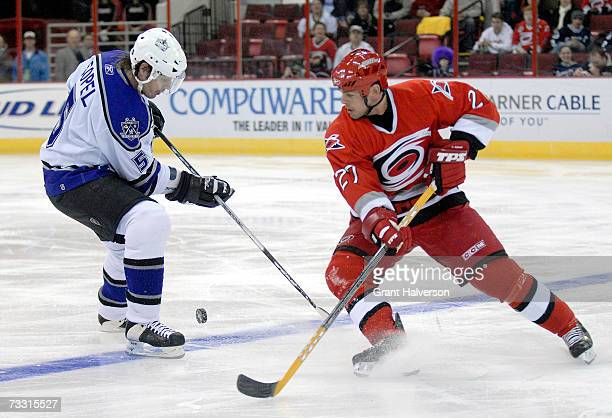 Craig Adams of the Carolina Hurricanes battles Brent Sopel of the Los Angeles Kings for the puck on February 13, 2007 at the RBC Center in Raleigh,...