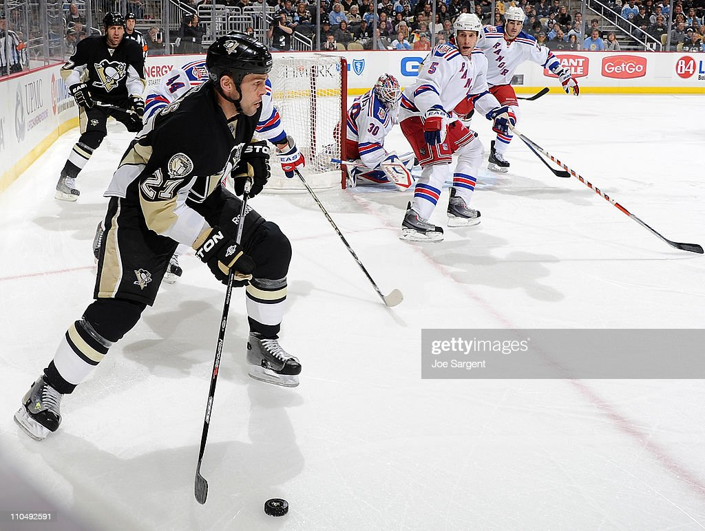Craig Adams #27 of the Pittsburgh Penguins controls the puck in front of the defense of Dan Girardi #5 of the New York Rangers on March 20, 2011 at Consol Energy Center in Pittsburgh, Pennsylvania. New York won the game 5-2.