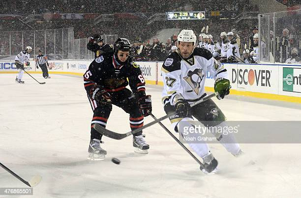 Craig Adams of the Pittsburgh Penguins tries for a backhand shot past Andrew Shaw of the Chicago Blackhawks during the 2014 NHL Stadium Series game...