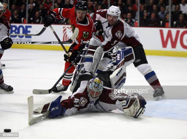 Craig Anderson of the Colorado Avalance sprawls to make a save as teammate Brett Clark battles with Andrew Ebbett of the Chicago Blackhawks at the...