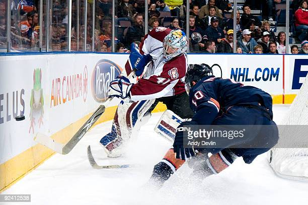 Craig Anderson of the Colorado Avalanche plays the puck past a defending Shawn Horcoff of the Edmonton Oilers at Rexall Place on October 27, 2009 in...