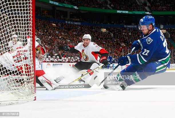 Craig Anderson of the Ottawa Senators deflects the puck away from Daniel Sedin of the Vancouver Canucks in front of Cody Ceci of the Senators during...
