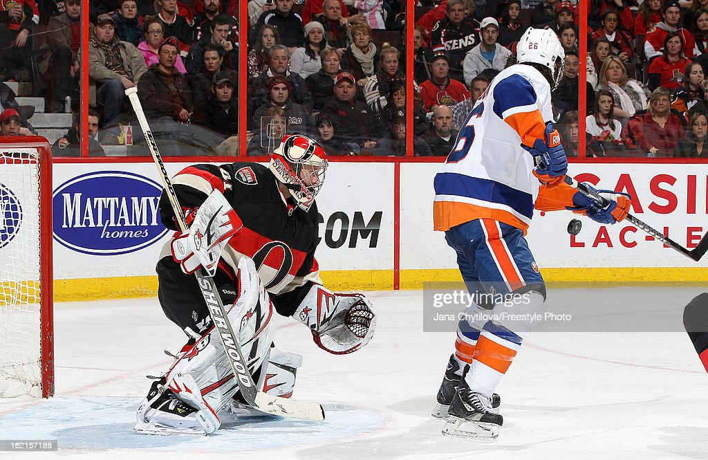 Craig Anderson #41 of the Ottawa Senators keeps his eyes on the puck as Matt Moulson #26 of the New York Islanders provides a screen, during an NHL game at Scotiabank Place on February 19, 2013 in Ottawa, Ontario, Canada.
