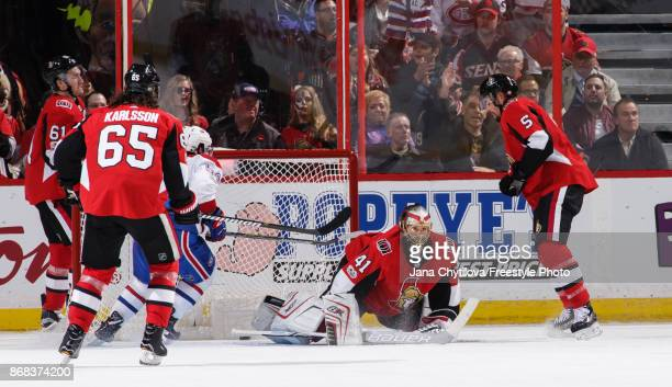 Craig Anderson of the Ottawa Senators kneels on the ice after allowing sixth goal scored by Brendan Gallagher of the Montreal Canadiens as Erik...