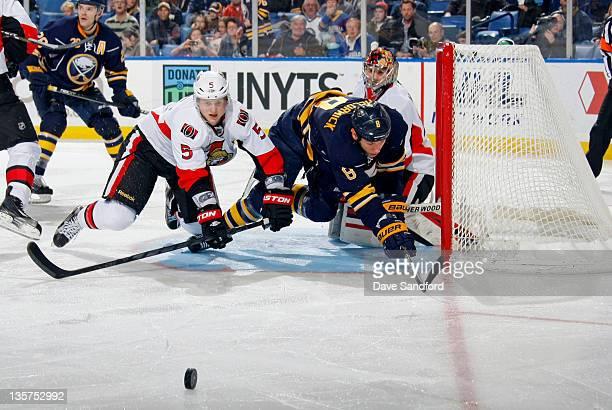 Craig Anderson of the Ottawa Senators looks on as Cody McCormick of the Buffalo Sabres battles with Brian Lee of the Ottawa Senators for the puck...