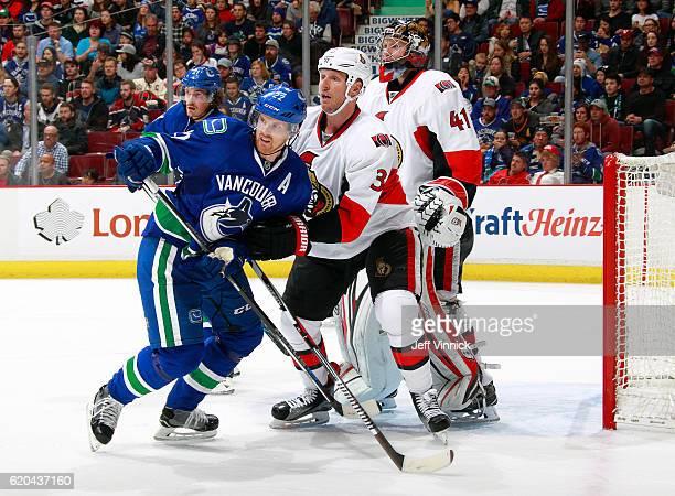 Craig Anderson of the Ottawa Senators looks on as Daniel Sedin of the Vancouver Canucks and Marc Methot of the Ottawa Senators look for the puck...