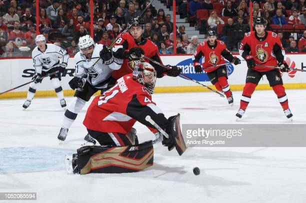 Craig Anderson of the Ottawa Senators makes a blocker save as teammate Maxime Lajoie battles for position against Alex Iafallo of the Los Angeles...