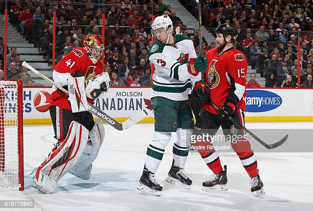 Craig Anderson of the Ottawa Senators makes a save against a screen by Charlie Coyle of the Minnesota Wild as teammate Zack Smith supports on the...