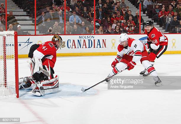 Craig Anderson of the Ottawa Senators makes a save against Elias Lindholm of the Carolina Hurricanes in overtime as Mike Hoffman back checks on the...
