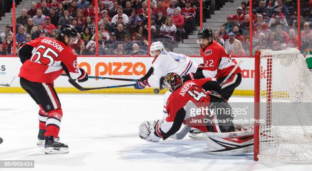 Craig Anderson of the Ottawa Senators makes a save against Paul Byron of the Montreal Canadiens as Erik Karlsson and Chris Kelly defend the net at...