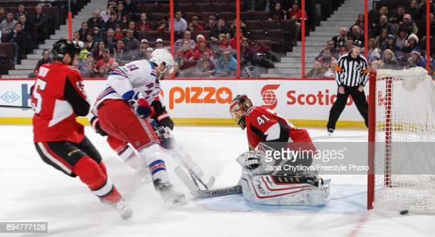 Craig Anderson of the Ottawa Senators makes a save against Rick Nash of the New York Rangers as Cody Ceci of the Ottawa Senators defends the net at...