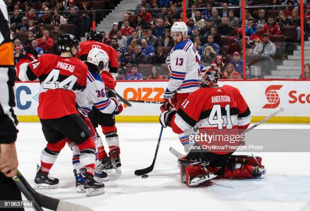 Craig Anderson of the Ottawa Senators makes a save as Kevin Hayes of the New York Rangers looks for a tip and JeanGabriel Pageau and Cody Ceci of the...