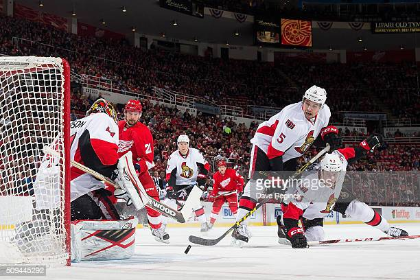 Craig Anderson of the Ottawa Senators makes a save as teammates Cody Ceci and Ryan Dzingel follow the puck during an NHL game against the Detroit Red...