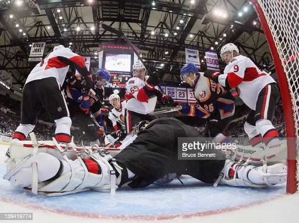 Craig Anderson of the Ottawa Senators makes the save as Erik Karlsson assists in their game against the New York Islanders at the Nassau Veterans...