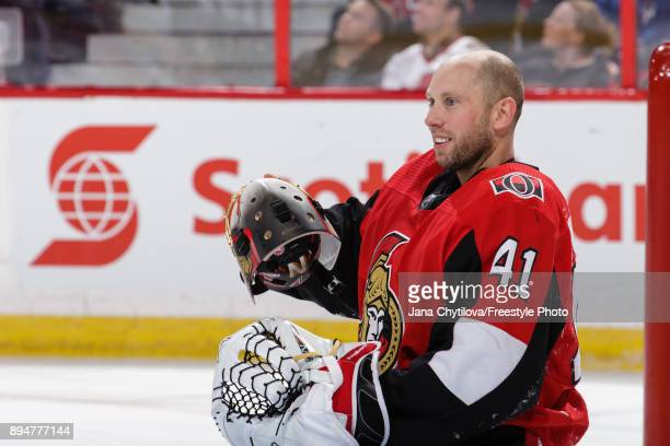 Craig Anderson of the Ottawa Senators puts his mask back on after it was knocked off during a play against the New York Rangers at Canadian Tire...