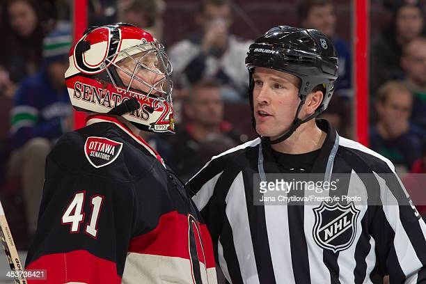 Craig Anderson of the Ottawa Senators talks with linesman Steve Barton during an NHL game against the Vancouver Canucks at Canadian Tire Centre on...