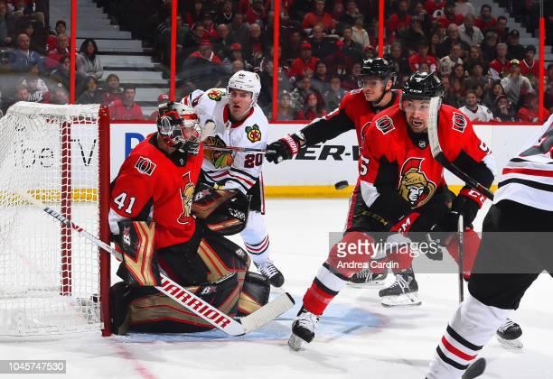 Craig Anderson of the Ottawa Senators tracks the puck with teammates Mark Borowiecki and Cody Ceci and Brandon Saad of the Chicago Blackhawks...