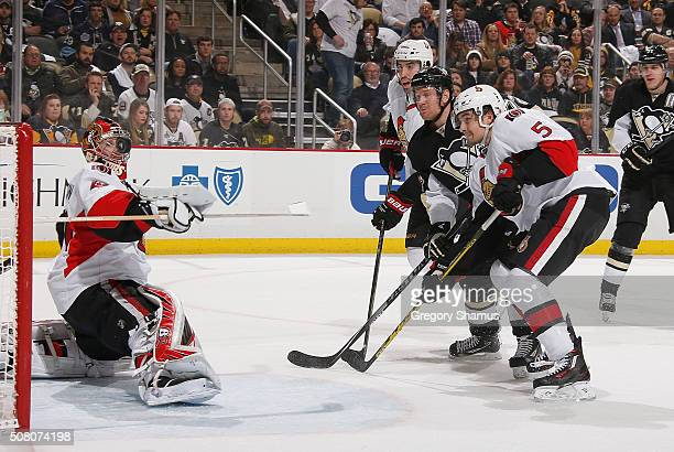 Craig Anderson of the Ottawa Senators watches the loose puck while Jared Cowen and Cody Ceci of the Ottawa Senators battle for position against...