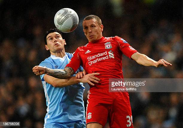 Craig Bellamy of Liverpool goes up for a header with Gareth Barry of Manchester City during the Carling Cup Semi Final First Leg match between...