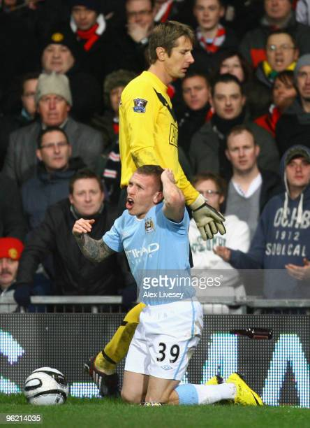 Craig Bellamy of Manchester City reacts after being hit by objects thrown from the crowd during the Carling Cup Semi Final second leg match between...