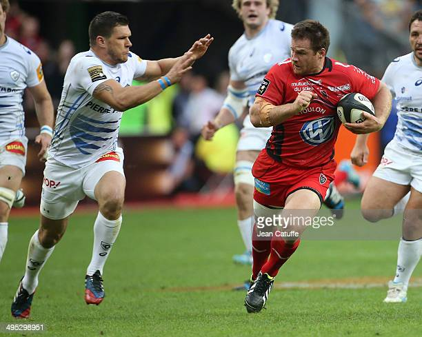 Craig Burden of RC Toulon runs with the ball despite Remy Grosso of Castres Olympique during the Top 14 Final between RC Toulon and Castres Olympique...