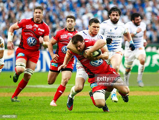 Craig Burden of the Rugby Club Toulonnais is tackled by Remy Grosso of Castres Olympique during the Top 14 Final game at Stade de France on May 31...