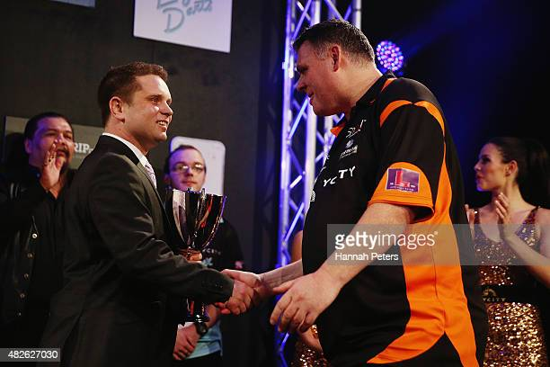 Craig Caldwell receives the trophy after winning the Super League Darts Final between Warren Parry and Craig Caldwell at Sky City on August 1 2015 in...