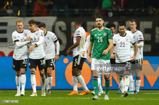 Craig Cathcart of Northern Ireland reacts as Leon Goretzka celebrates with Julian Brandt of Germany after scoring his team's second goal during the...