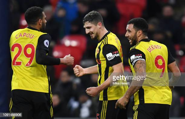 Craig Cathcart of Watford celebrates with teammates Etienne Capoue and Troy Deeney after scoring his team's first goal during the Premier League...