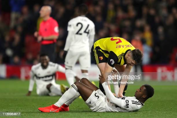 Craig Cathcart of Watford consoles Ryan Sessegnon of Fulham who looks dejected as Fulham are relegated due to the result in the Premier League match...