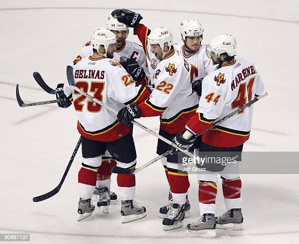Craig Conroy and Jarome Iginla of the Calgary Flames celebrate with teammate Martin Gelinas after Gelinas scored the team's first goal against the...