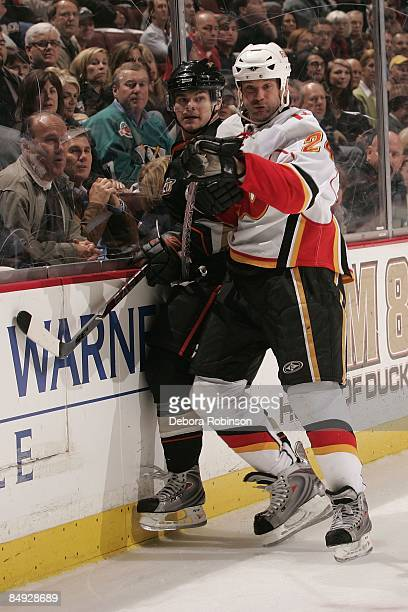 Craig Conroy of the Calgary Flames checks Chris Kunitz of the Anaheim Ducks into the boards during the game on February 11 2009 at Honda Center in...