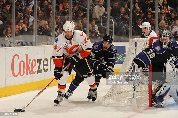Craig Conroy of the Calgary Flames skates with the puck behind the goal against Brad Richardson of the Los Angeles Kings at Staples Center on...