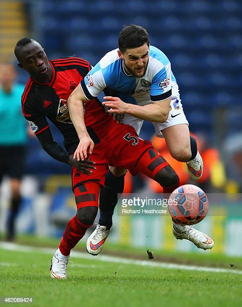Craig Conway of Blackburn Rovers is challenged by Modou Barrow of Swansea City during the FA Cup Fourth Round match between Blackburn Rovers and...