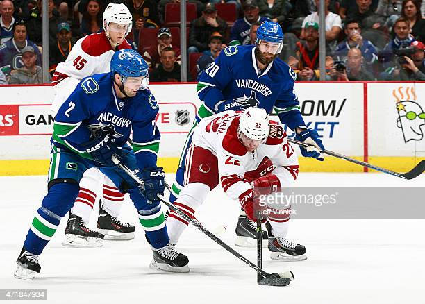 Craig Cunningham of the Arizona Coyotes and Dan Hamhuis of the Vancouver Canucks battle for a loose puck during their NHL game at Rogers Arena April...