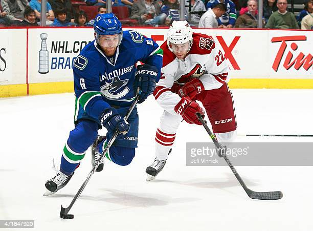 Craig Cunningham of the Arizona Coyotes looks on as Yannick Weber of the Vancouver Canucks skates up ice with the puck during their NHL game at...