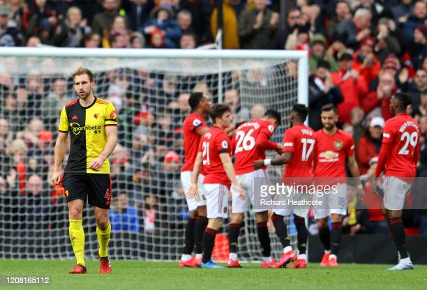 Craig Dawson of Watford looks dejected as Mason Greenwood of Manchester United celebrates with teammates after scoring his team's third goal during...