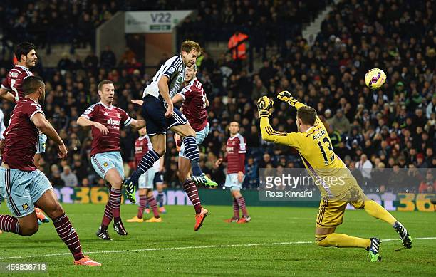 Craig Dawson of West Brom heads and scores the opening goal past Adrian of West Ham during the Barclays Premier League match between West Bromwich...