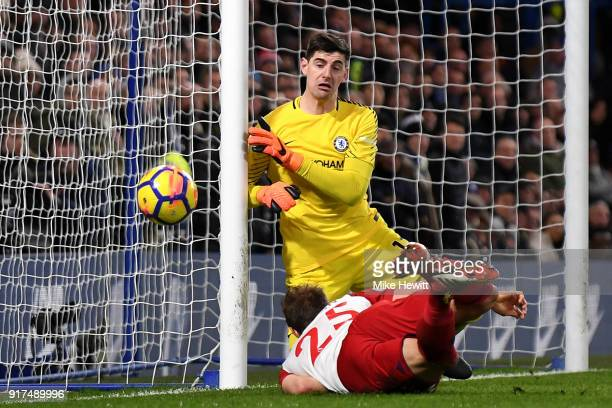 Craig Dawson of West Bromwich Albion wins a header as Thibaut Courtois of Chelsea watches the ball go wide during the Premier League match between...