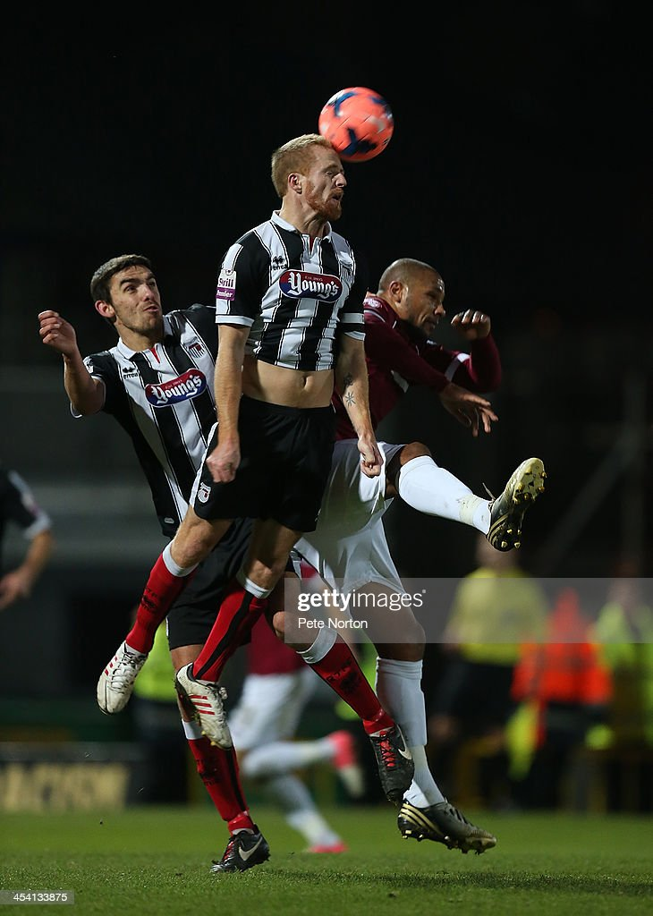Craig Disley of Grimsby Town heads the ball away from Clive Platt of Northampton Town and team mate Shaun Pearson during the FA Cup with Budweiser Second Round match between Grimsby Town and Northampton Town at Blundell Park on December 7, 2013 in Grimsby, England.