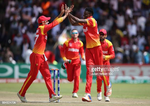 Craig Ervine and Blessing Muzarabani of Zimbabwe celebrate the wicket of Chris Gayle of The West Indies during The Cricket World Cup Qualifier...