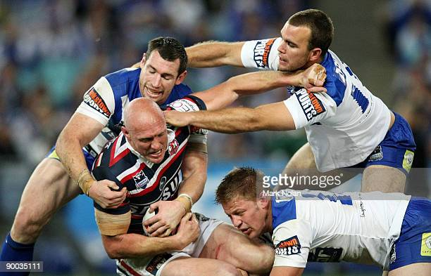 Craig Fitzgibbon of the Roosters is tackled by Michael Hodgson Gary Warburton and David Stagg of the Bulldogs during the round 24 NRL match between...