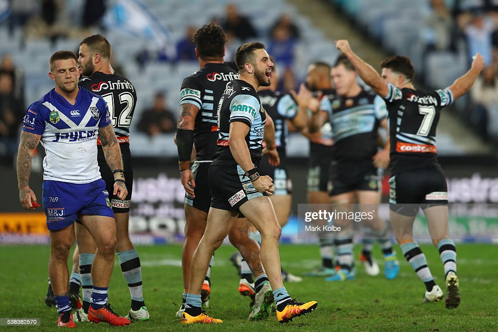 Craig Garvey of the Bulldogs looks dejected as Jack Bird of the Sharks celebrates victory during the round 13 NRL match between the Canterbury Bulldogs and the Cronulla Sharks at ANZ Stadium on June 6, 2016 in Sydney, Australia.