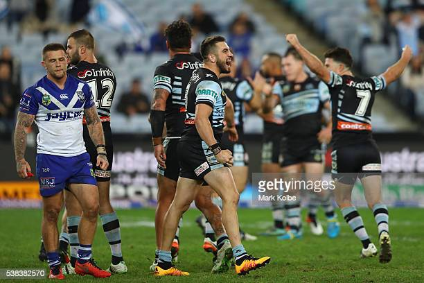 Craig Garvey of the Bulldogs looks dejected as Jack Bird of the Sharks celebrates victory during the round 13 NRL match between the Canterbury...